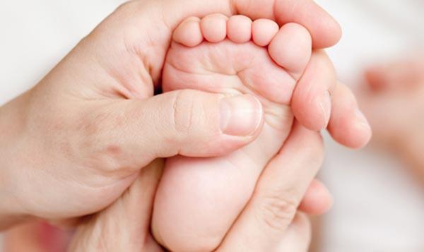 Ножка ребёнка в руках взрослого