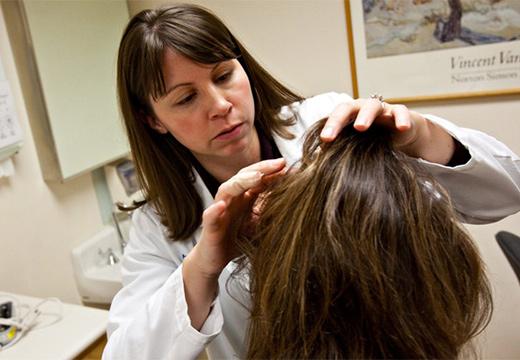 врач осматривает голову пациента