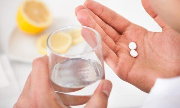 В руках мужчины сткан воды и две таблетки картинка