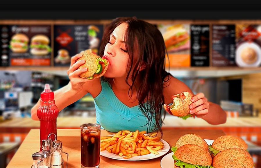 Девушка ест гамбургер за столом в бургерной картинка